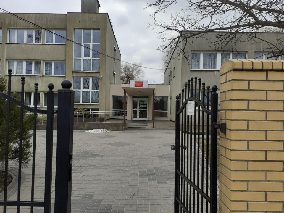 Zdjęcie przedstawia wejście główne do budynku siedziby WOIK przy ul. 6 Sierpnia 1/5 w Warszawie z odległości furtki wejściowej na teren WOIK